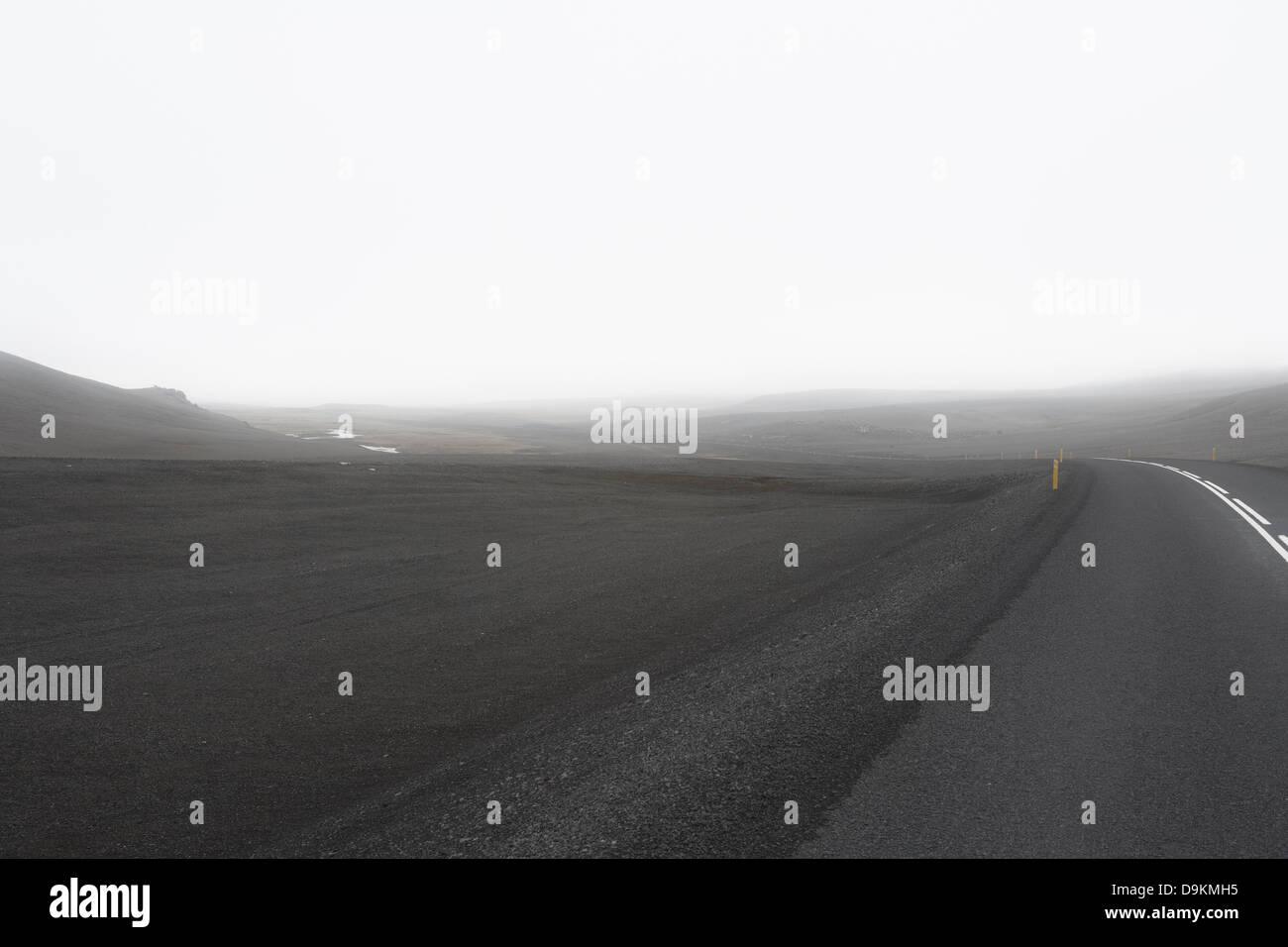 Grey road in empty landscape - Stock Image