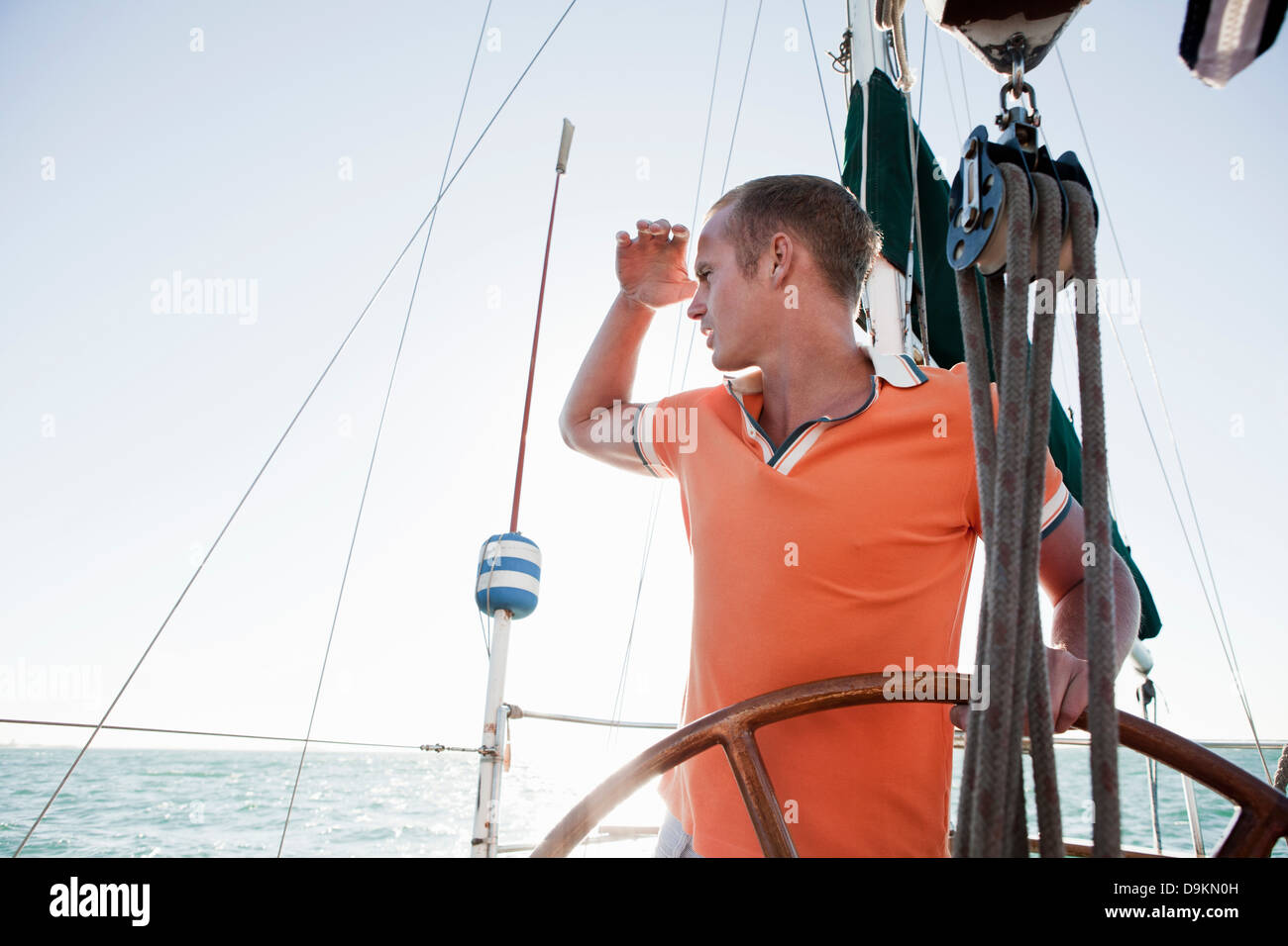 Young man steering yacht - Stock Image