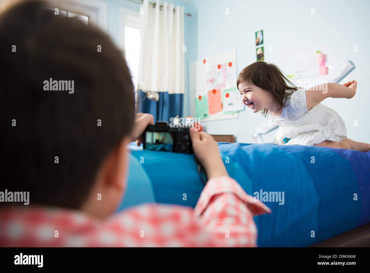 Boy taking pictures of sister play acting - Stock Image