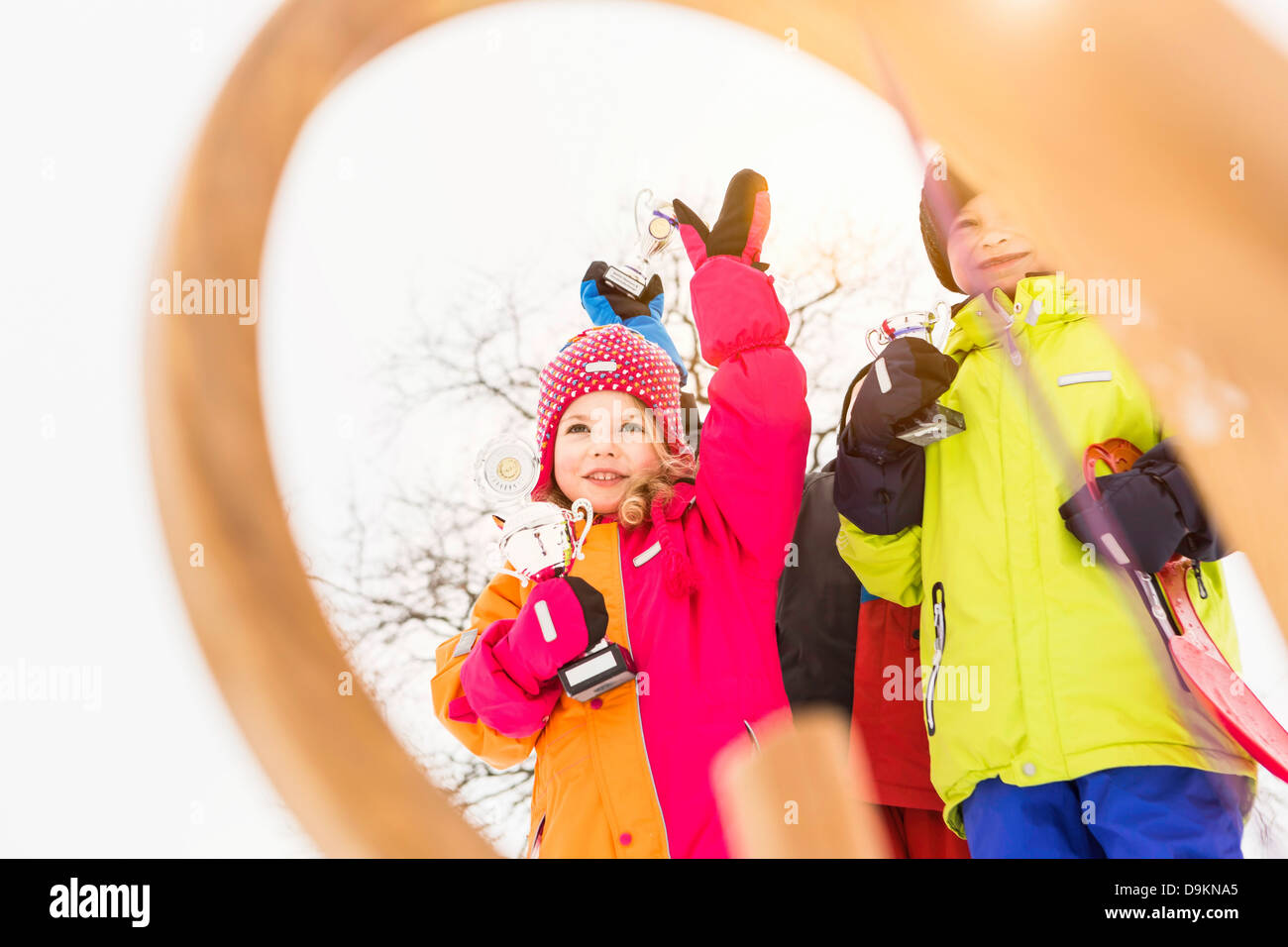 Girl in winter clothing holding trophy - Stock Image