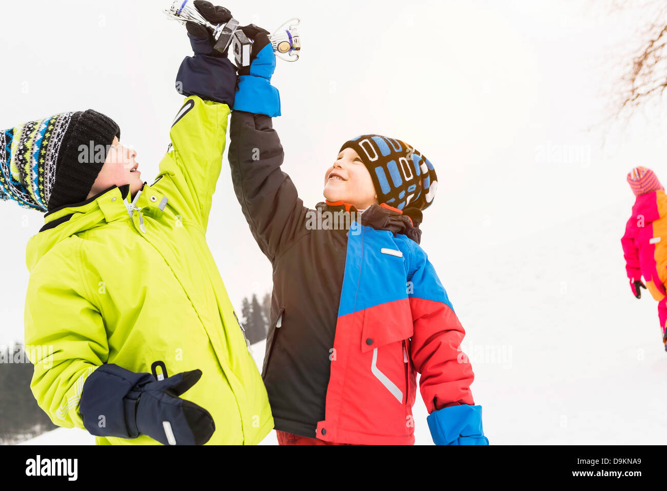 Two boys holding trophies up in the air - Stock Image