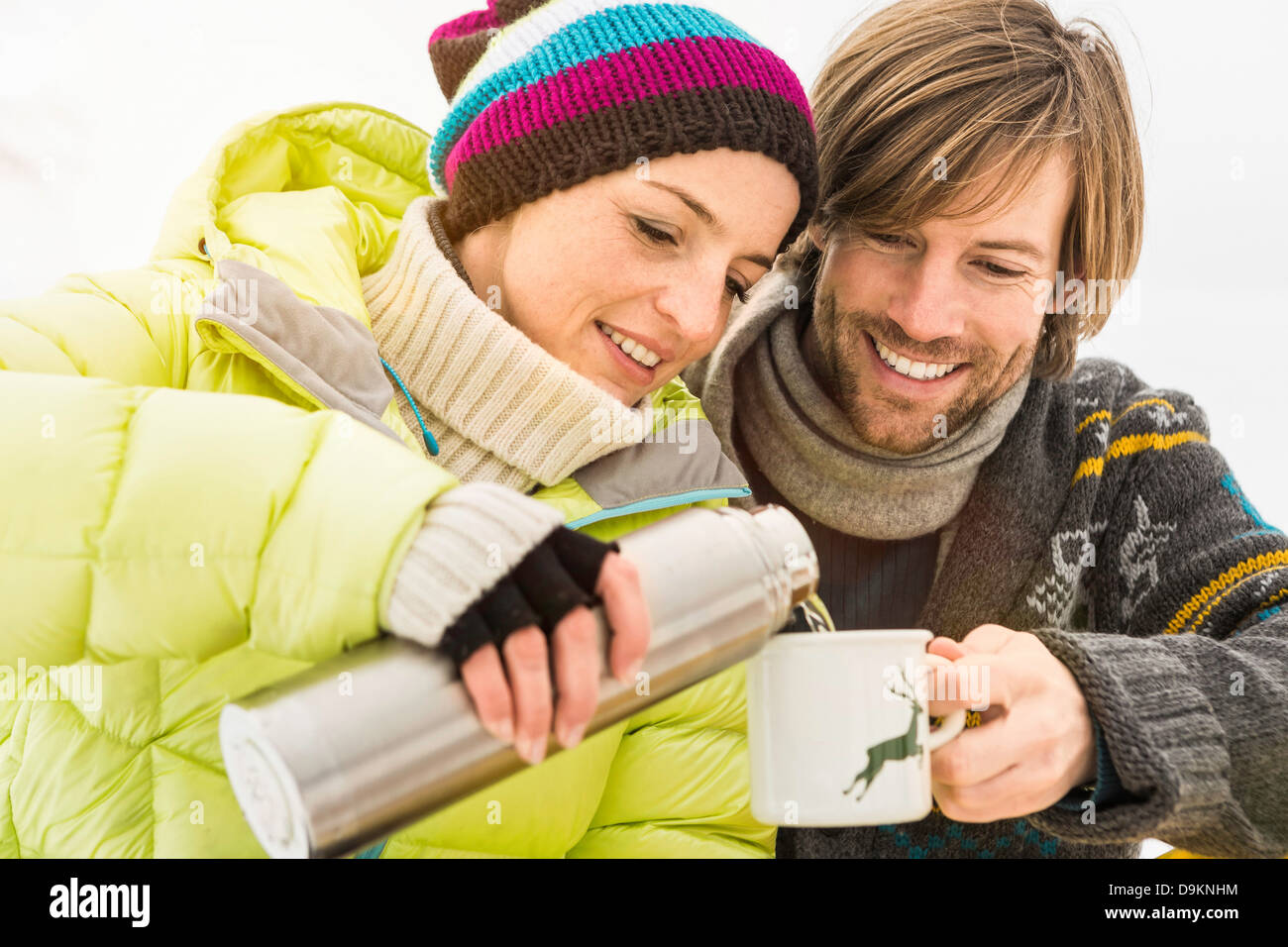 Woman pouring hot drink from flask, man holding mug - Stock Image