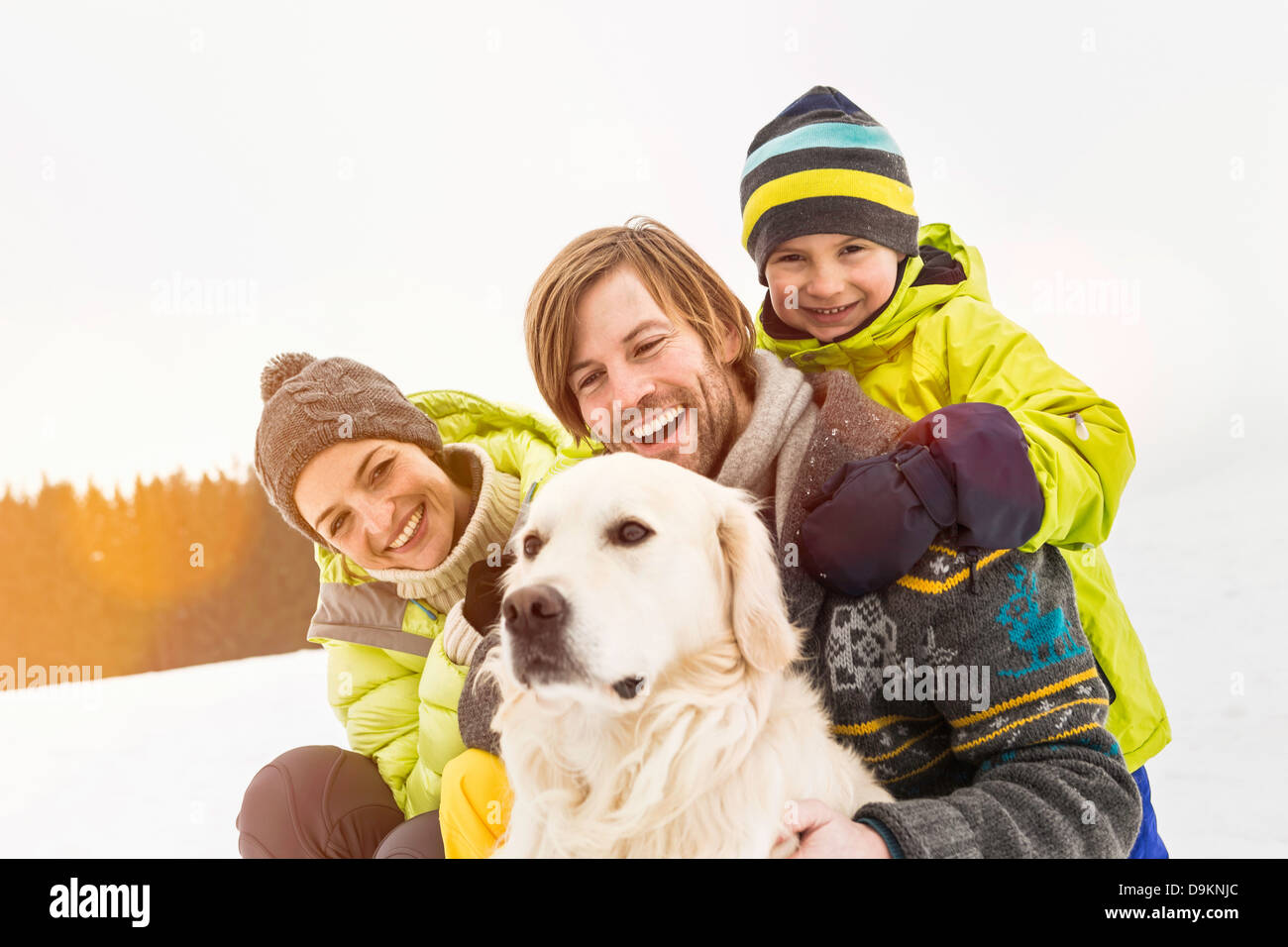 Parents and son with dog in snow - Stock Image
