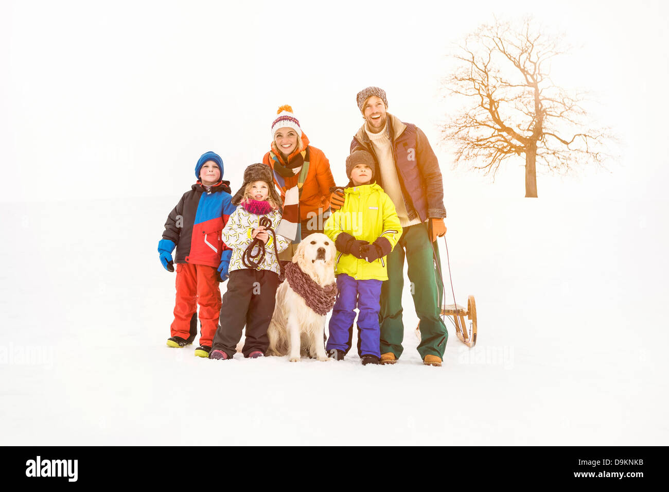 Family with three children standing in snow - Stock Image