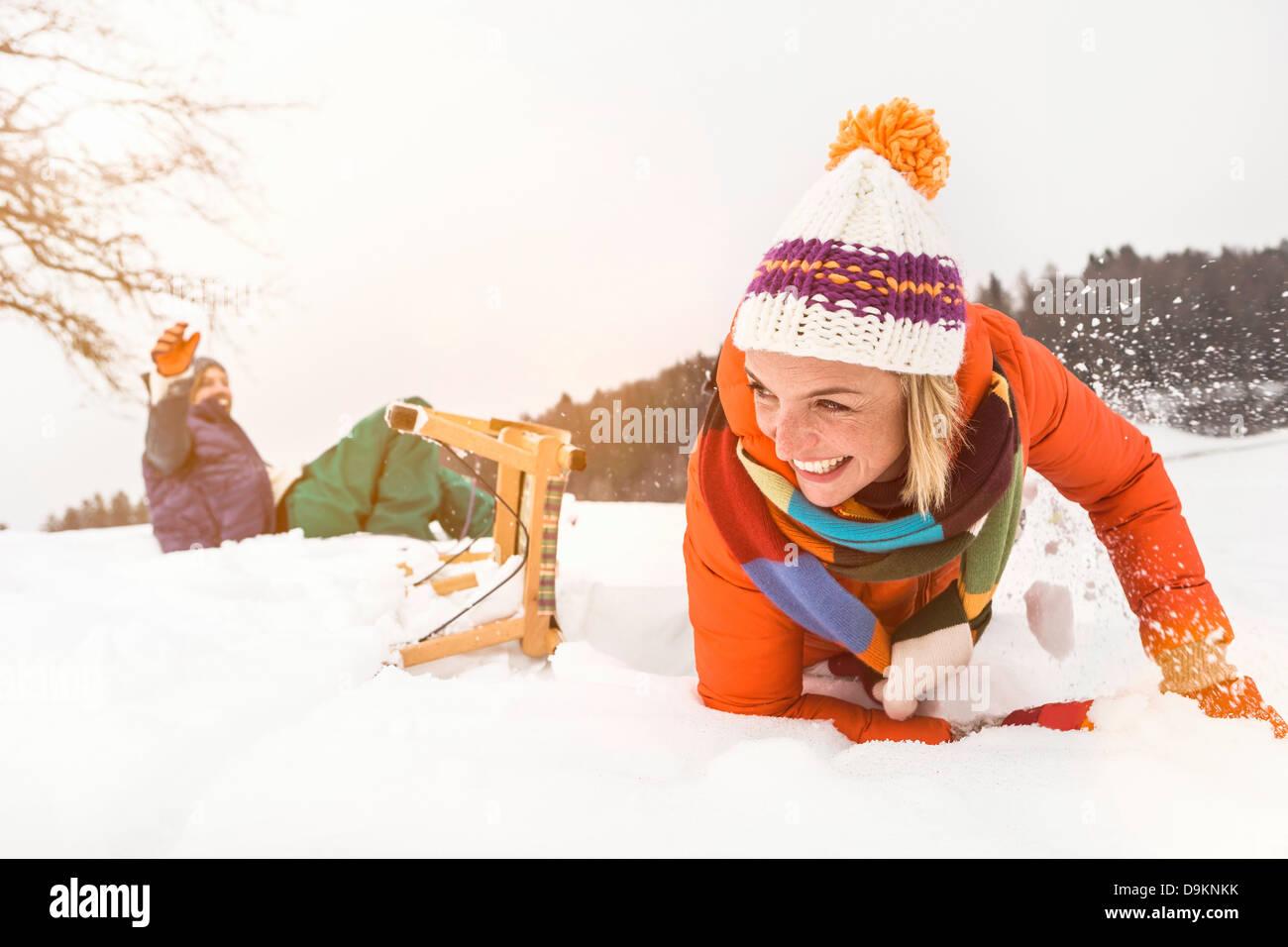 Couple falling off toboggan in snow - Stock Image