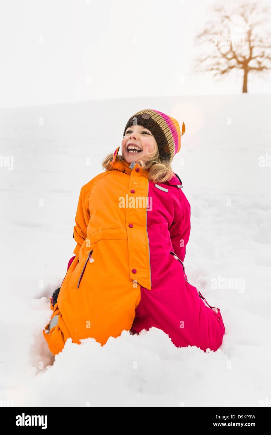 Portrait of girl wearing snowsuit kneeling on snow - Stock Image