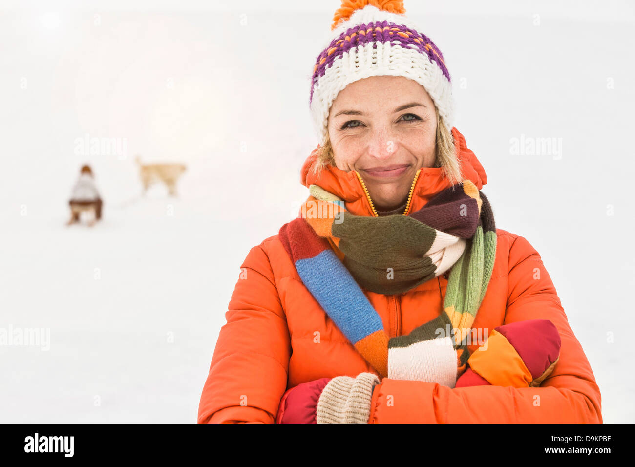 Woman wearing knit hat and striped scarf - Stock Image