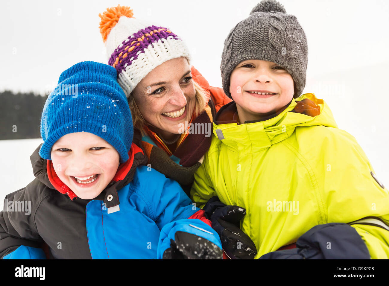 Mother with two boys wearing knit hats - Stock Image