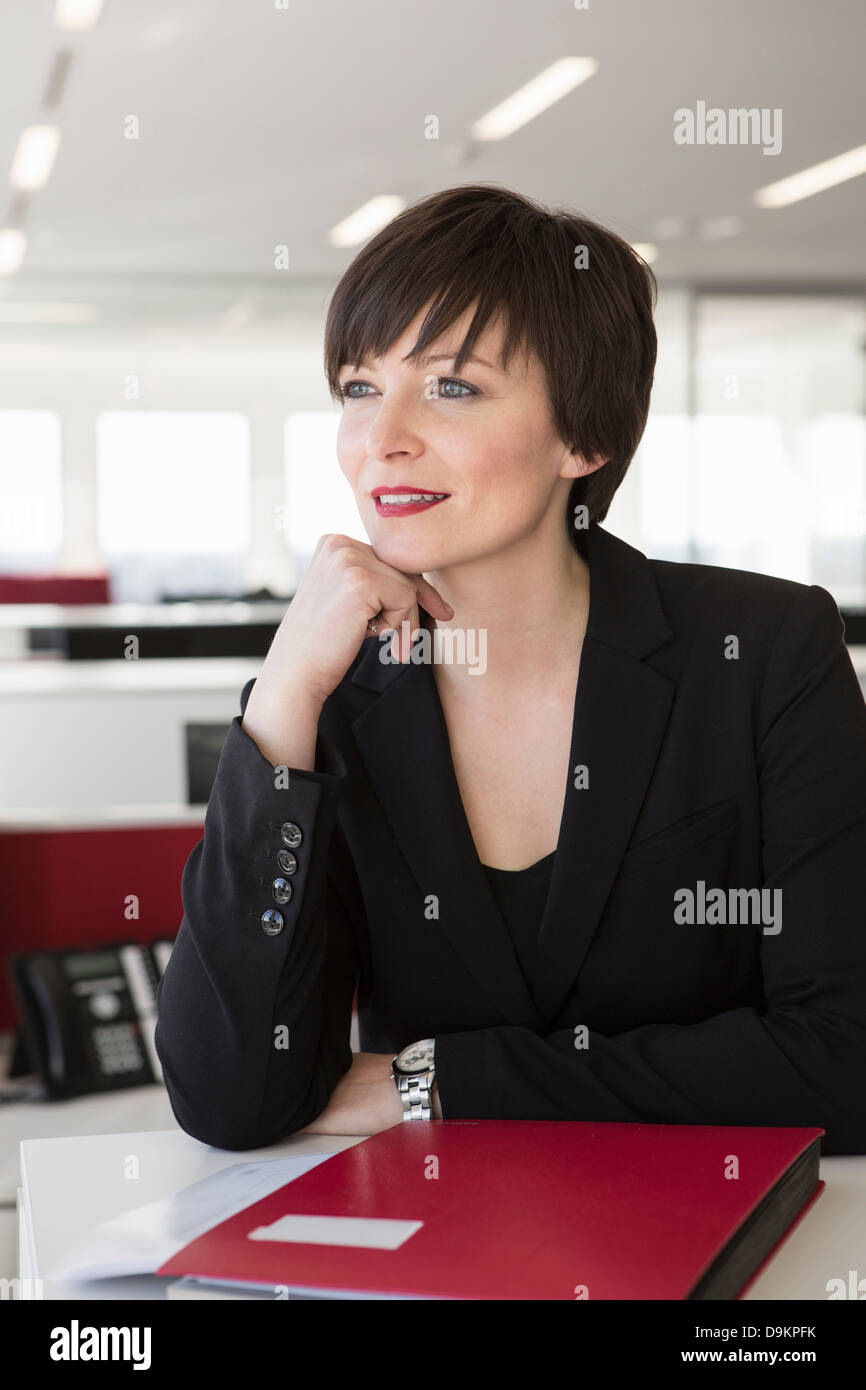 Businesswoman with hand on chin - Stock Image