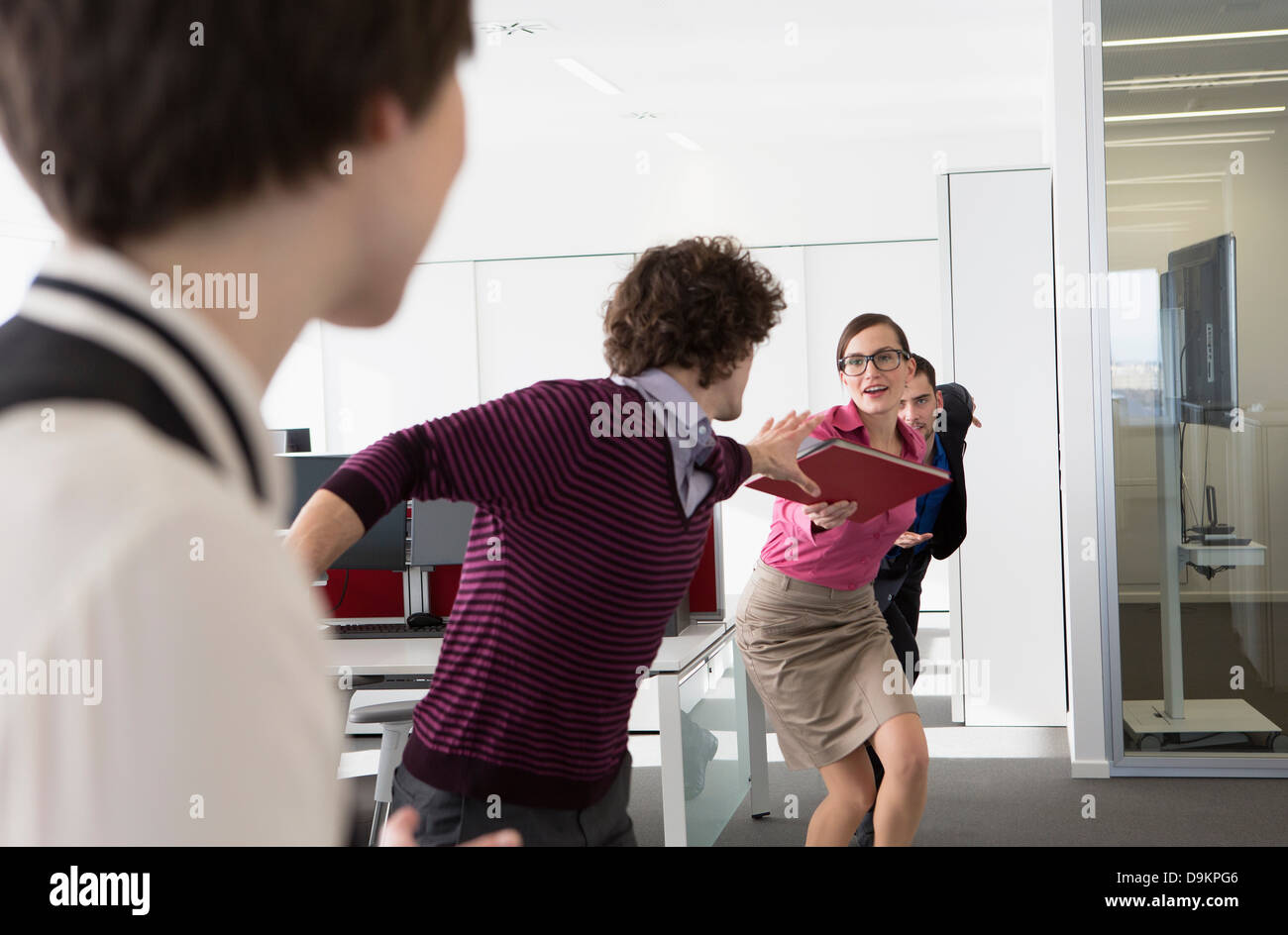 Office workers having relay race with file - Stock Image