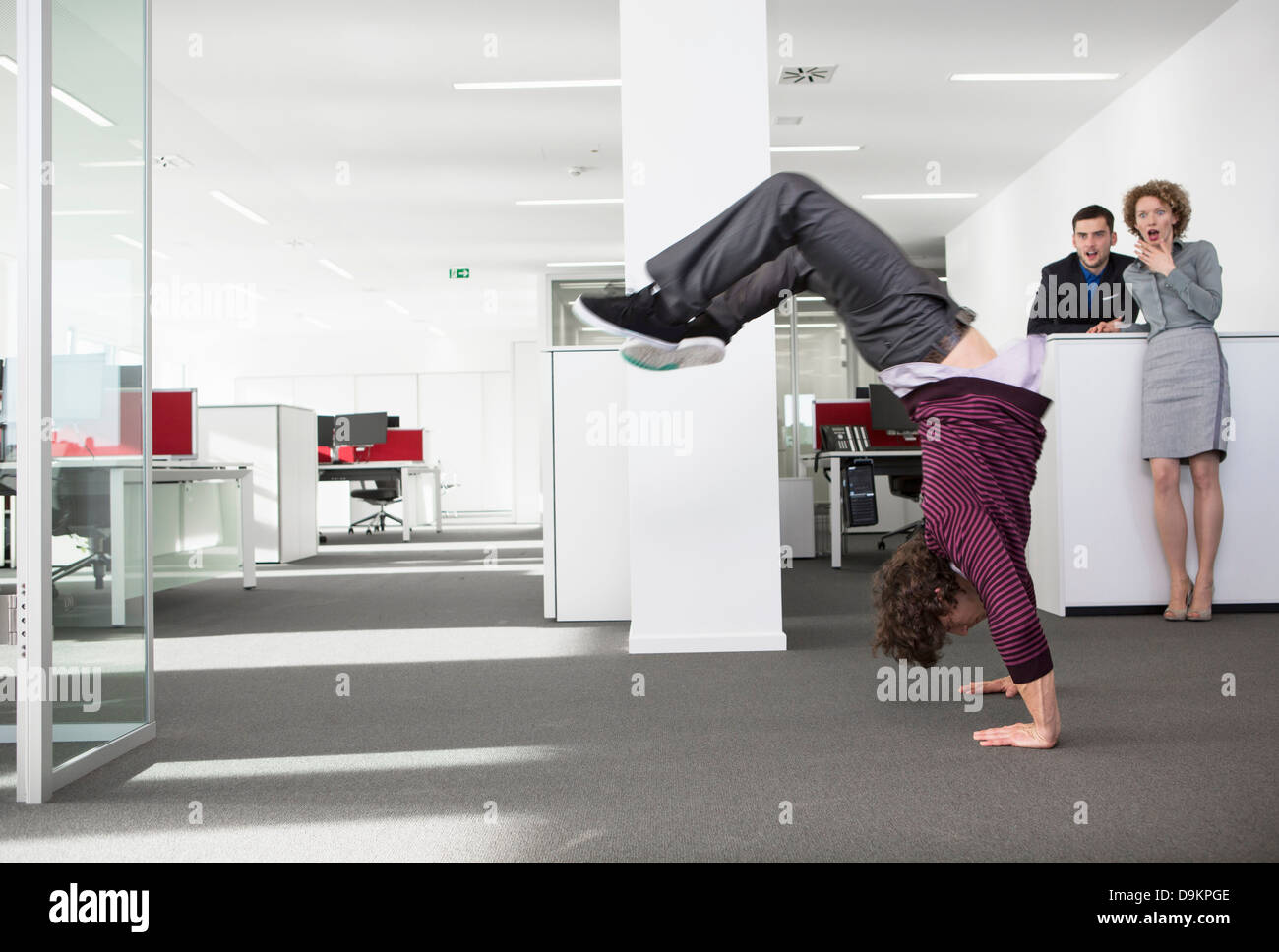 Office worker doing handstand, colleagues watching in shock - Stock Image