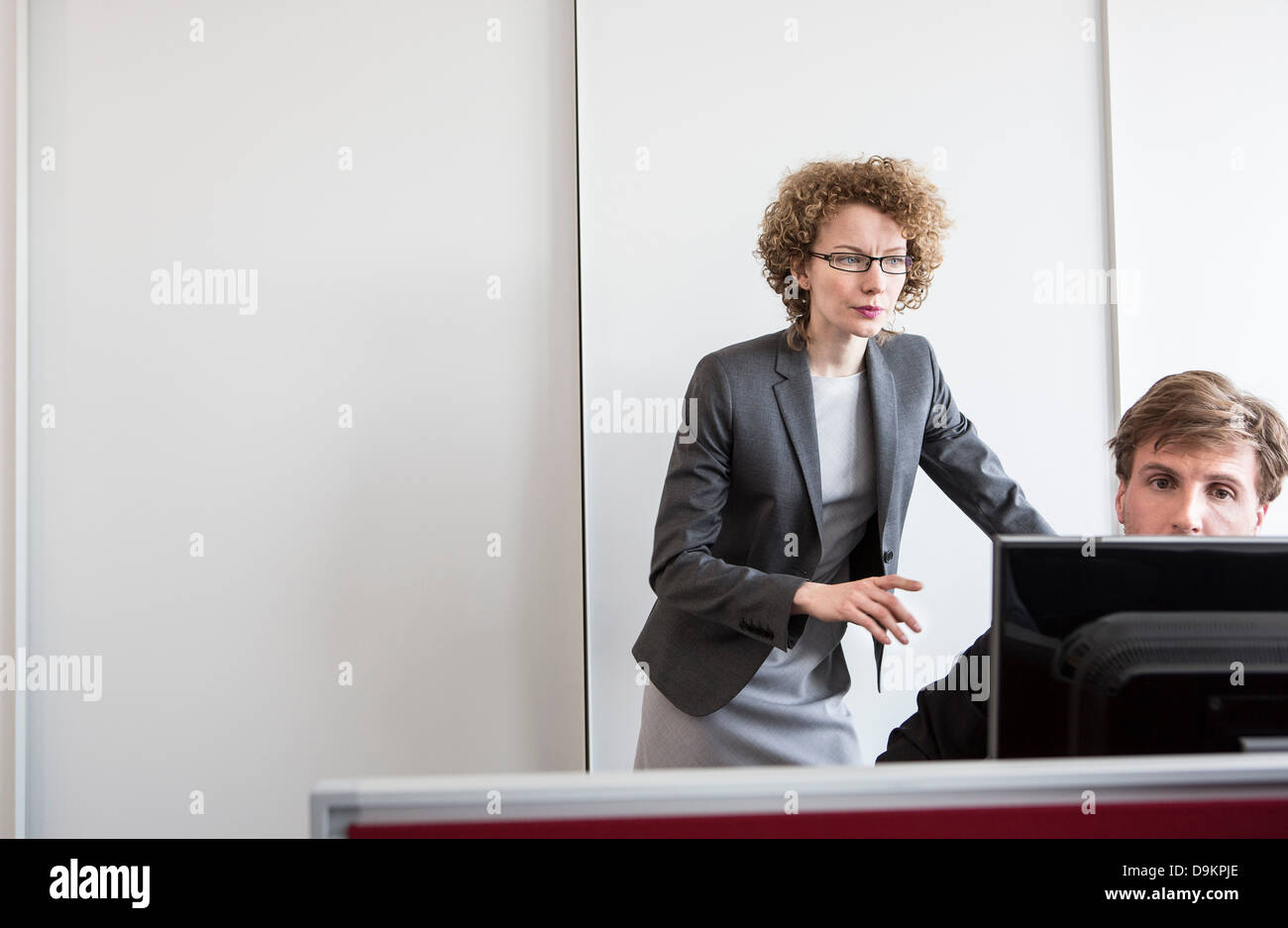 Businessman and businesswoman working in office - Stock Image