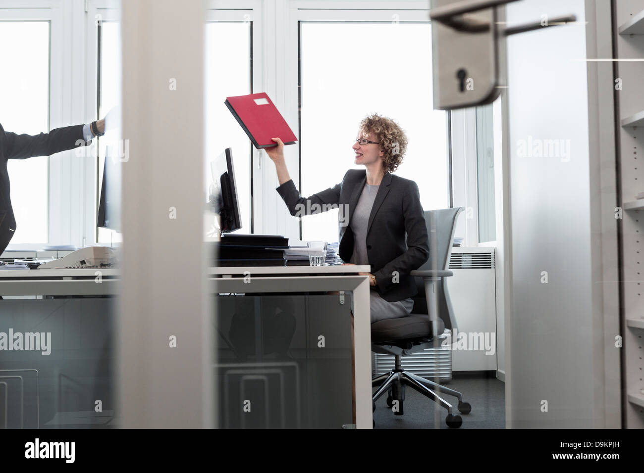 Businesswoman handing file to man in office - Stock Image
