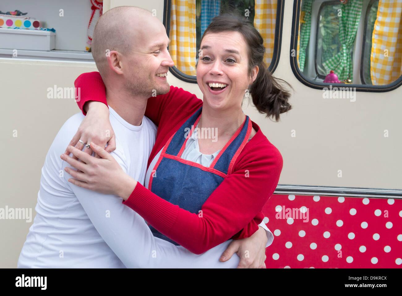 Mid adult couple embracing outside of caravan - Stock Image