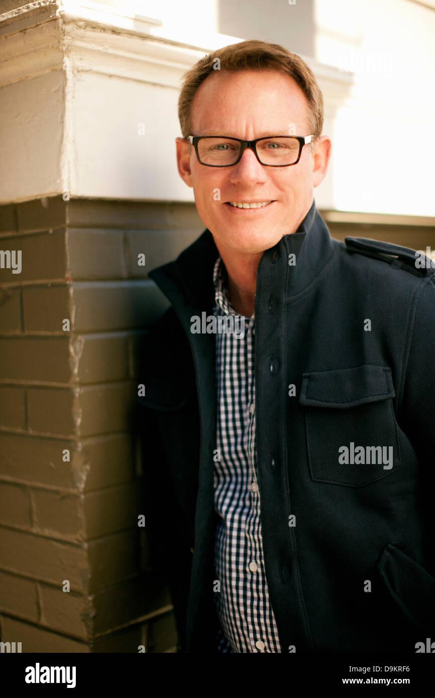 Man standing against brickwall Stock Photo