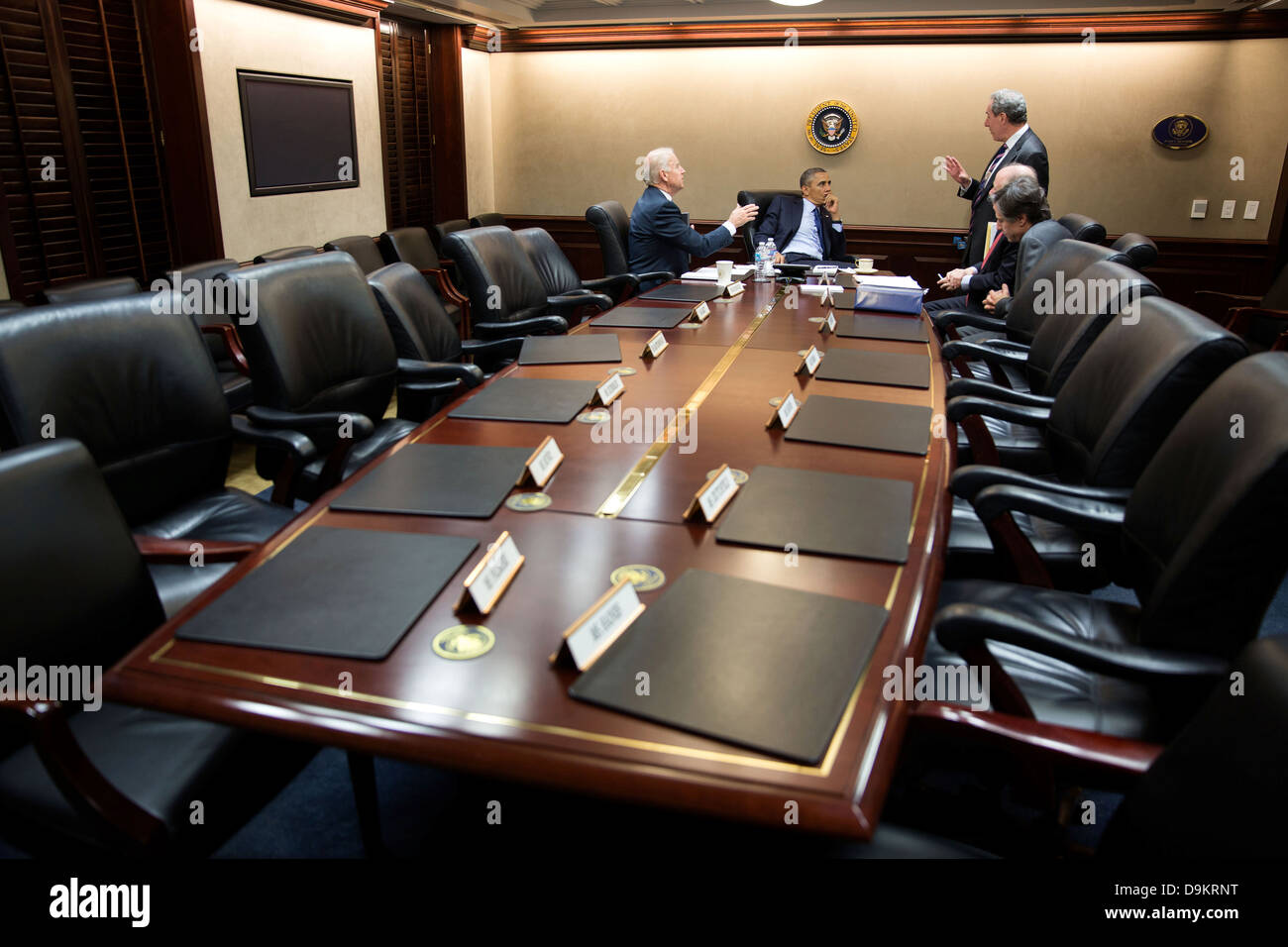 US President Barack Obama and Vice President Joe Biden talk with advisors following a National Security Staff meeting - Stock Image