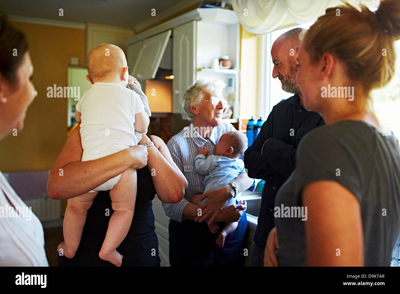 Family gathered in kitchen at home - Stock Image
