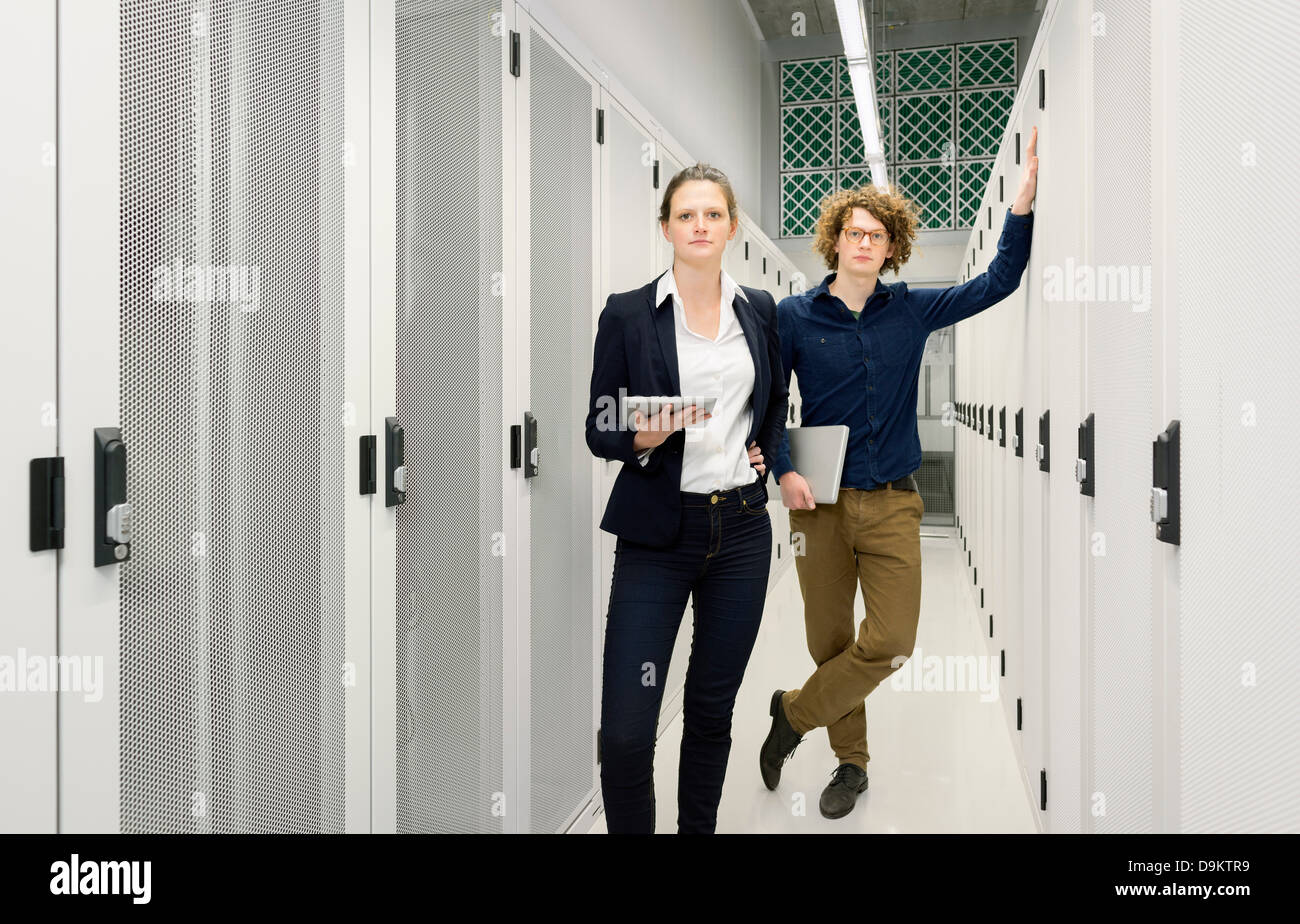 Two employees standing in data storage room - Stock Image