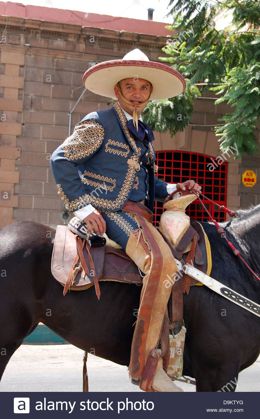 Modern day Mexican cowboy in parade on horseback looking at camera sitting  in the saddle with sombrero. ad0676e038d