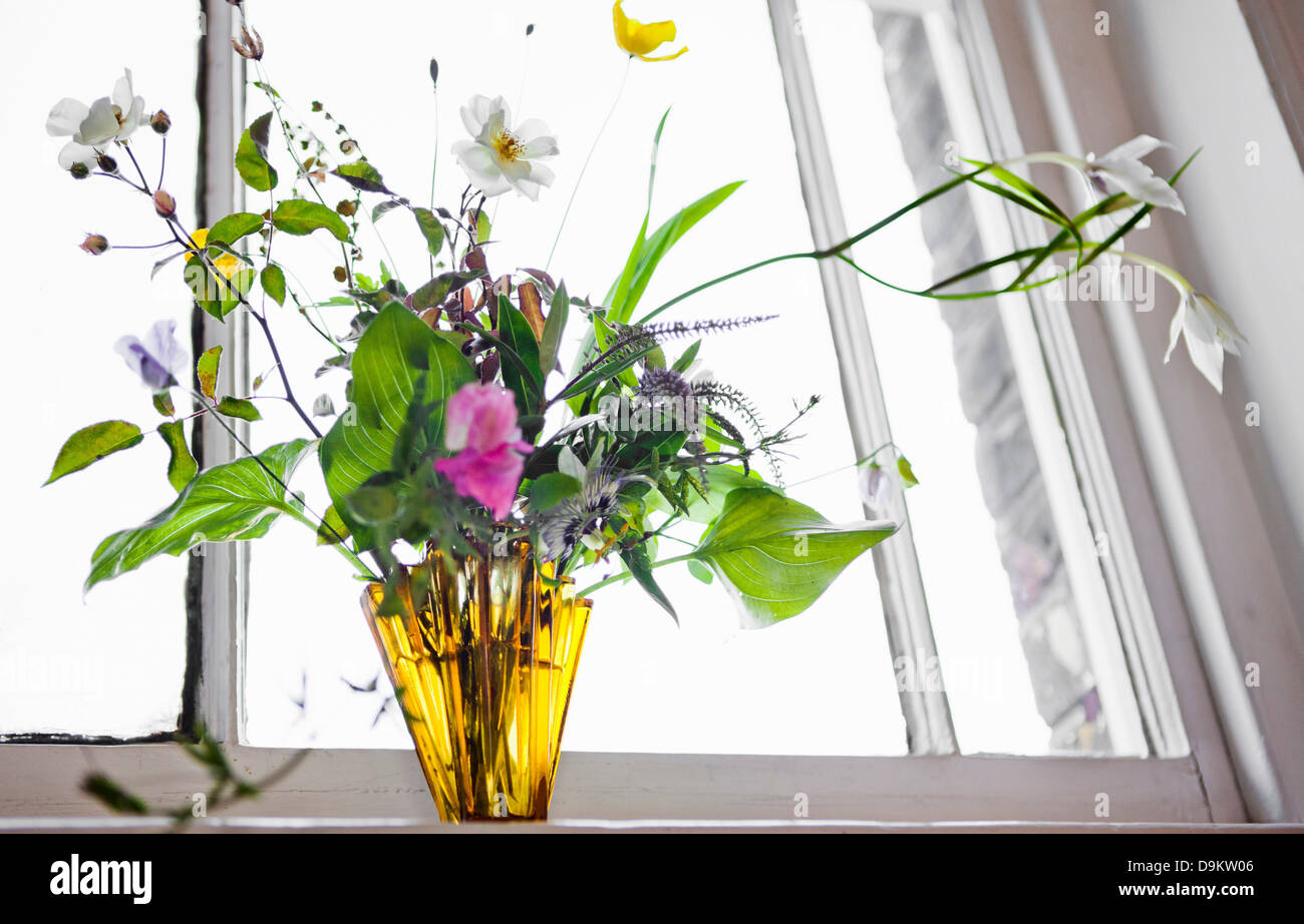 Flower arrangement in vase by window - Stock Image