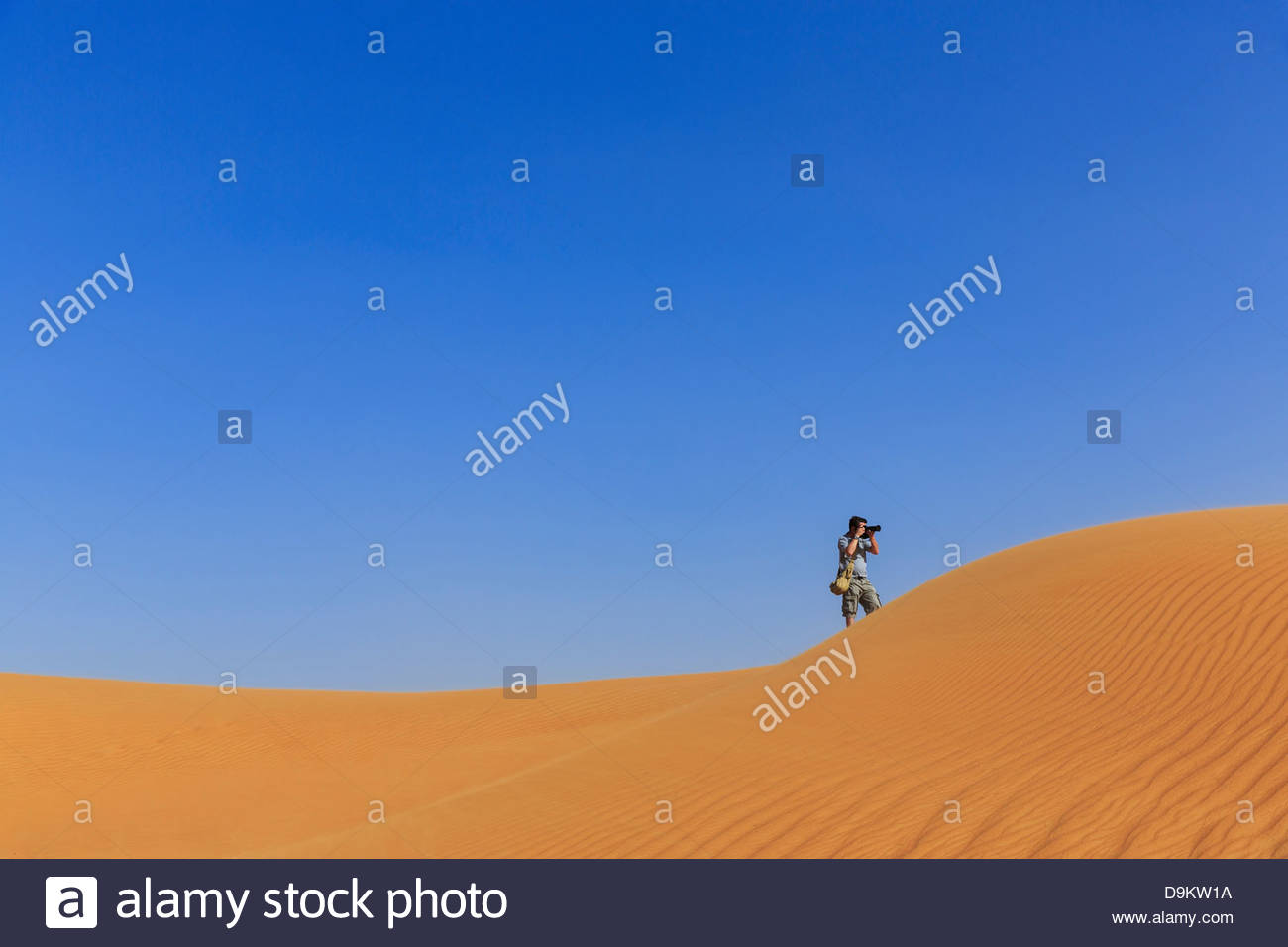 Man photographing in sand dunes in desert, Dubai, United Arab Emirates - Stock Image