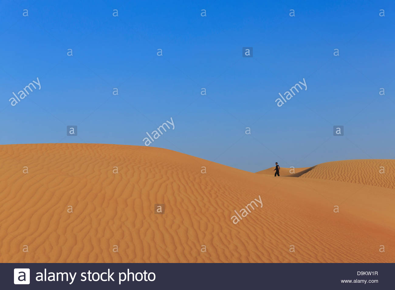 Man jogging in sand dunes in desert, Dubai, United Arab Emirates - Stock Image