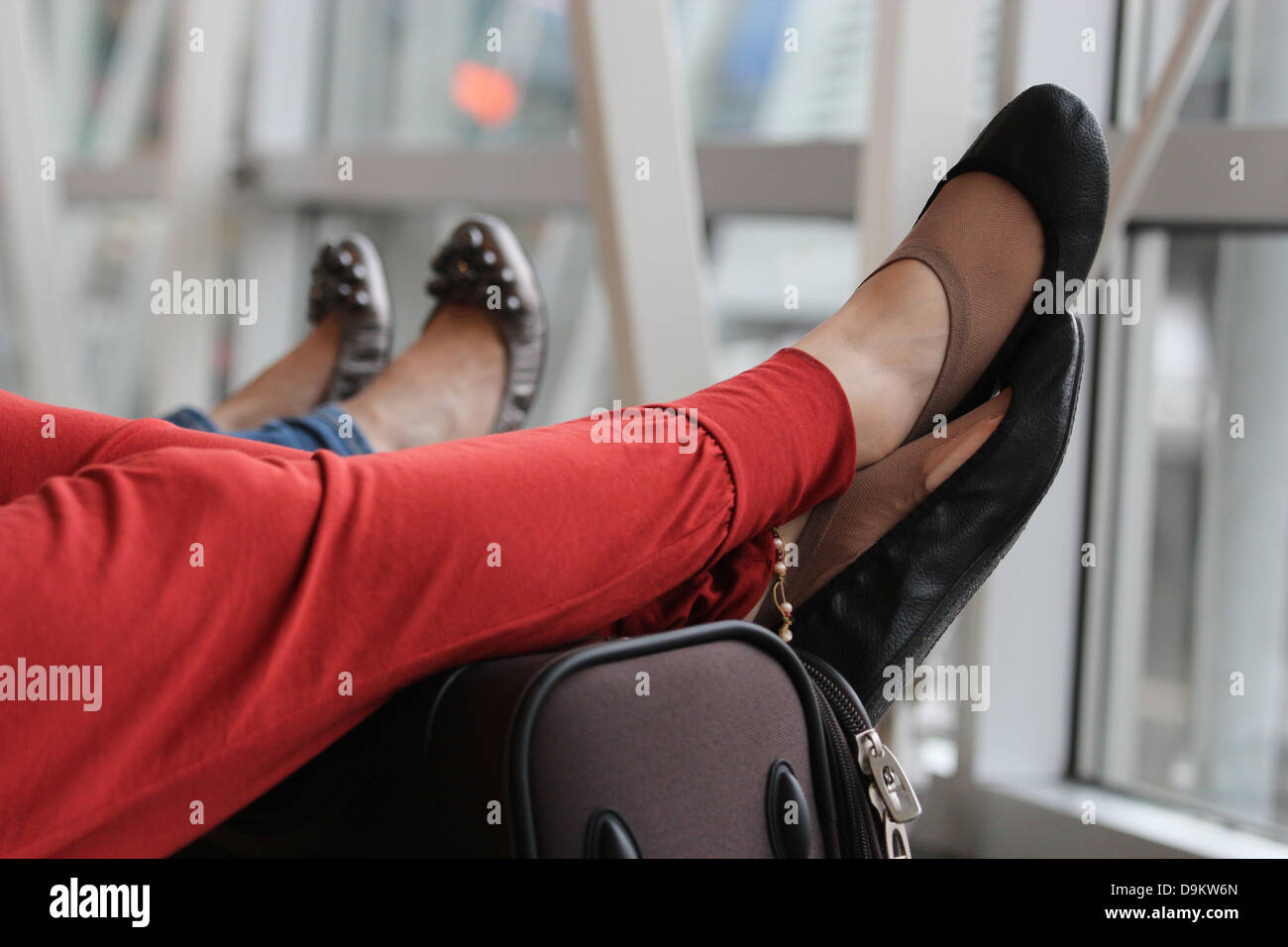 A weary traveller rests her tired, ballet pump & torn sock clad feet on  her suitcase whilst waiting for a flight - Stock Image