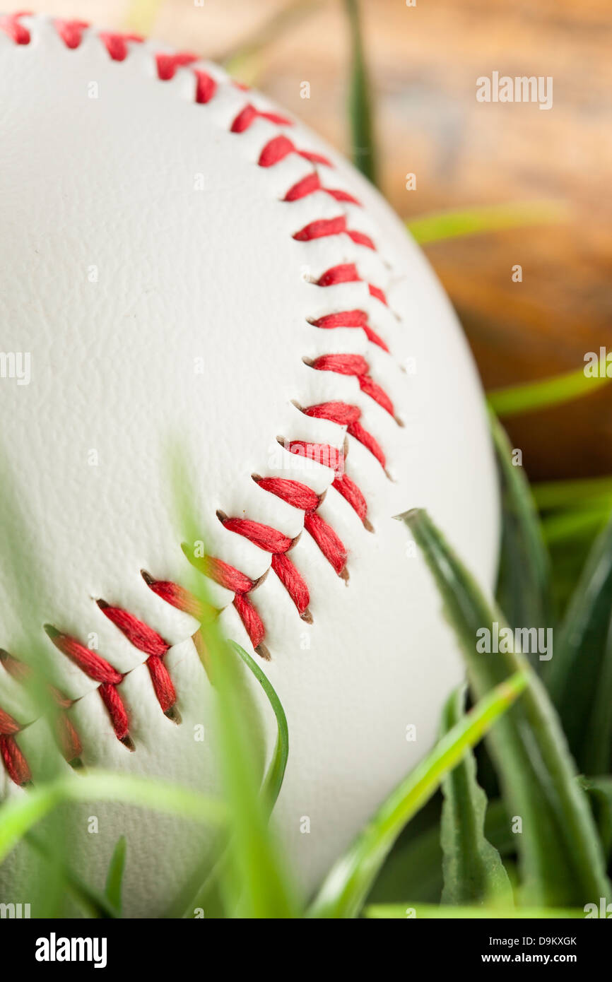 Brand New White Baseball in green grass with a bat - Stock Image