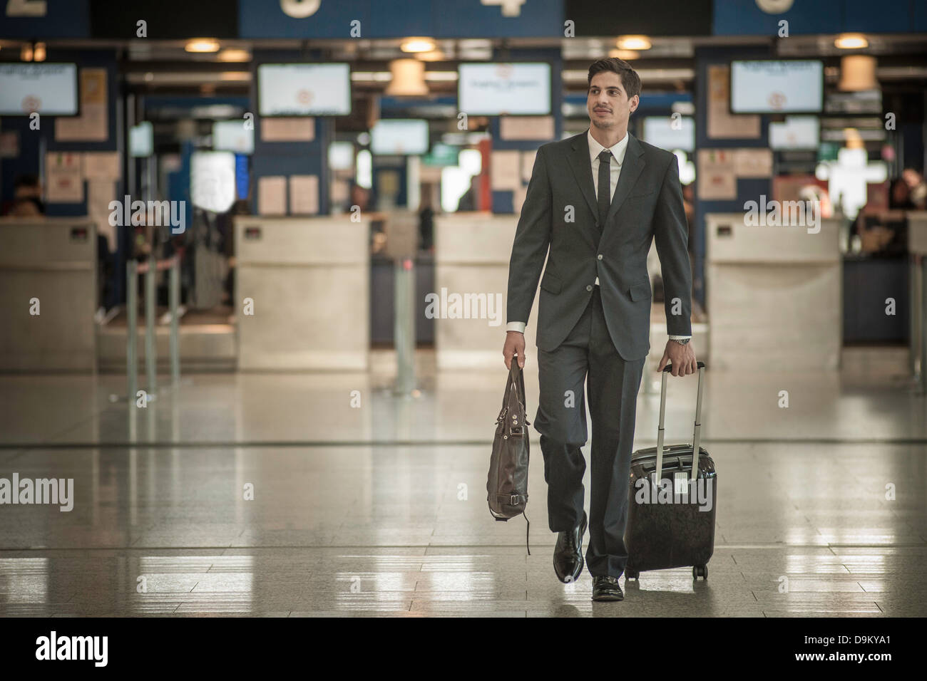 Young man with wheeled suitcase in airport - Stock Image
