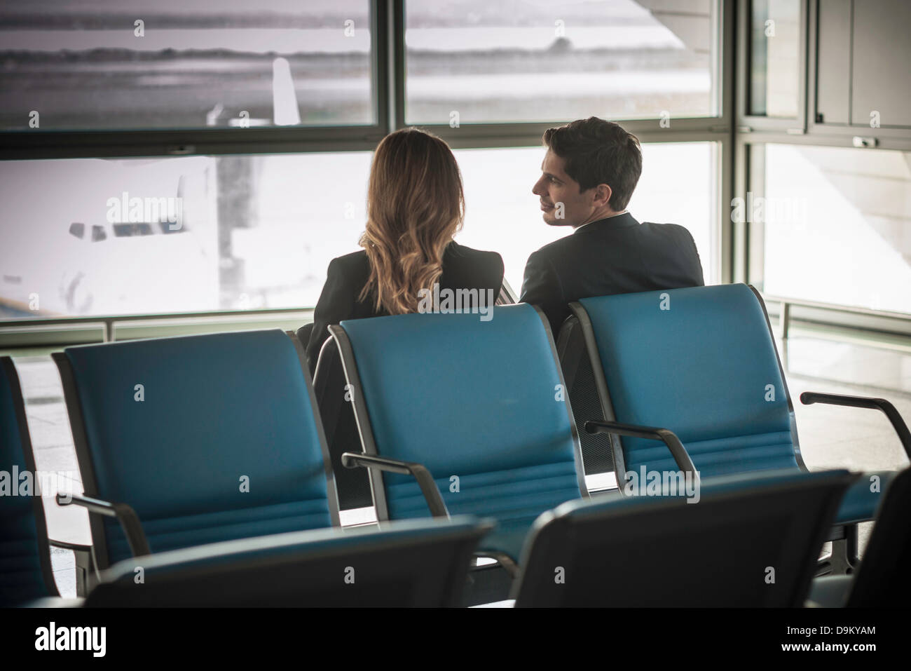 Businesspeople waiting in airport departure lounge - Stock Image