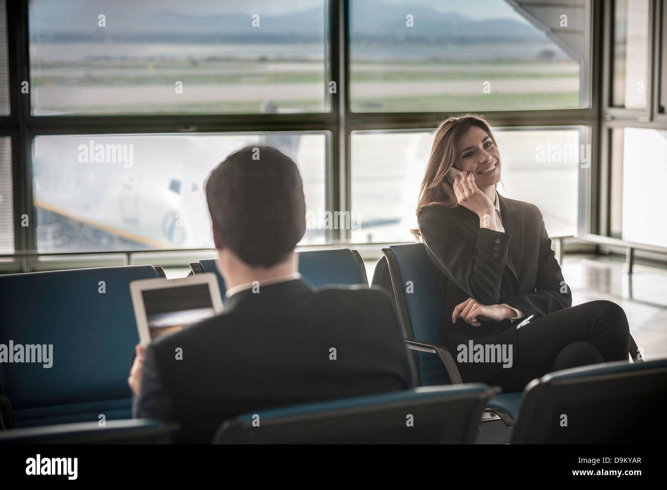 Businessman using digital tablet, businesswoman on mobile phone - Stock Image