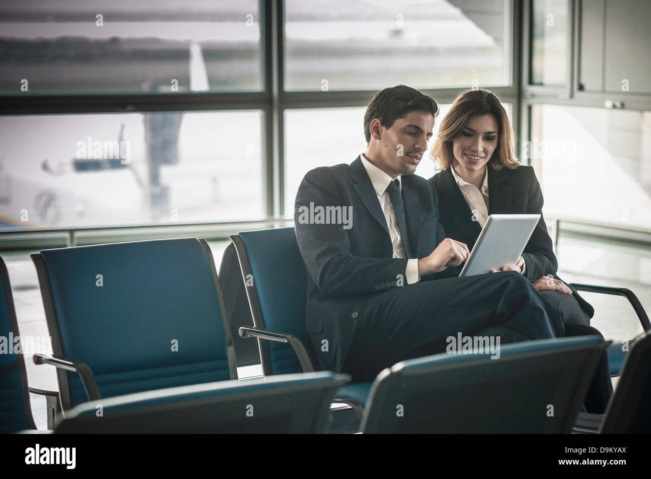 Businesspeople using digital tablet in airport departure lounge - Stock Image
