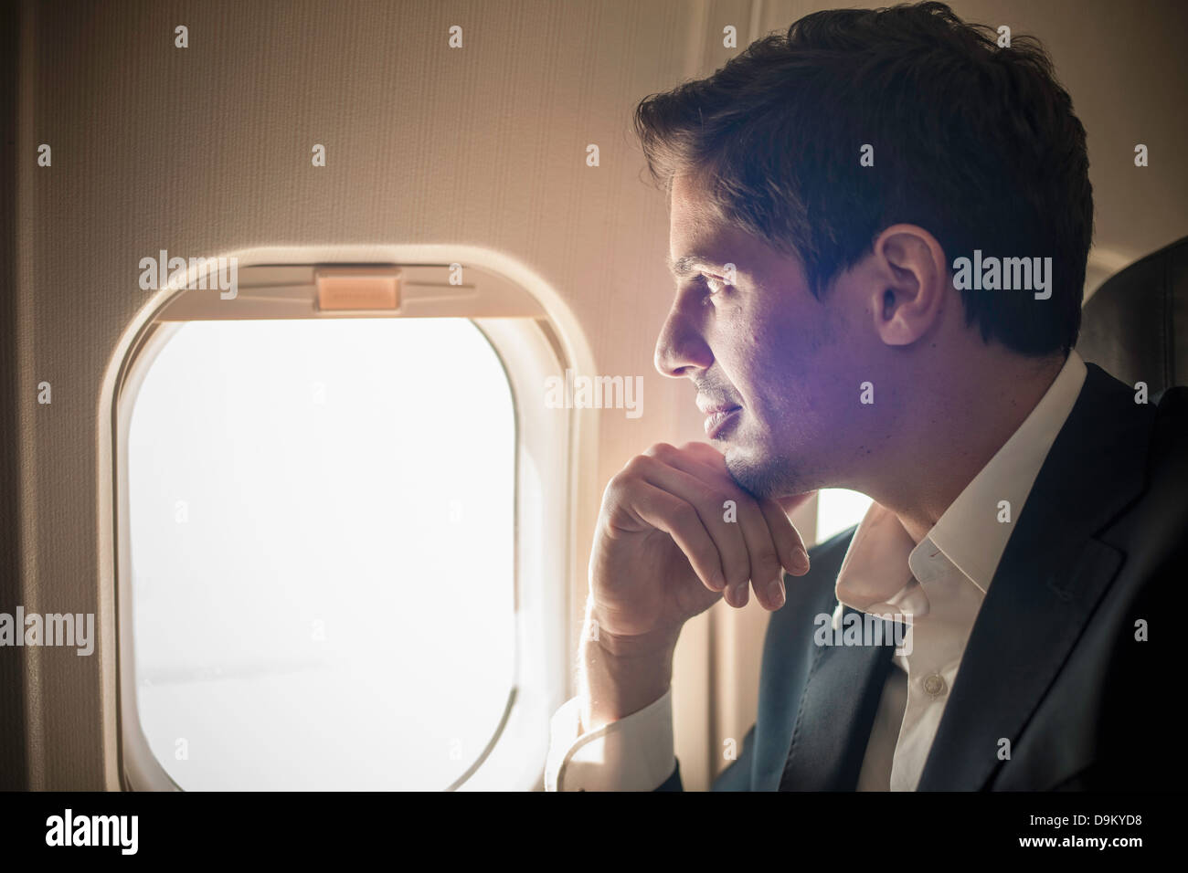 Male passenger looking out of aeroplane window - Stock Image