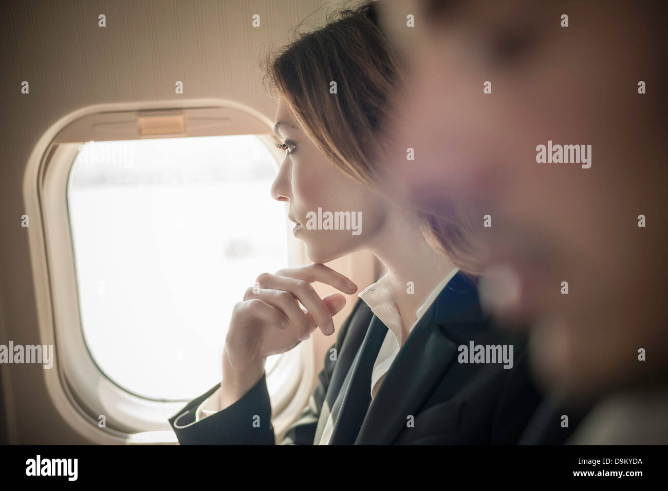 Female passenger looking out of aeroplane window - Stock Image