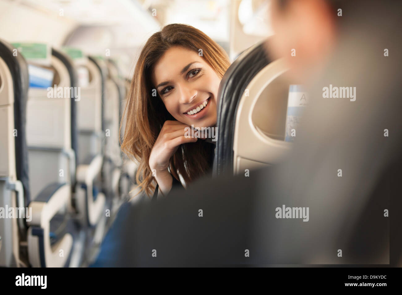 Female passenger turning around on aeroplane - Stock Image