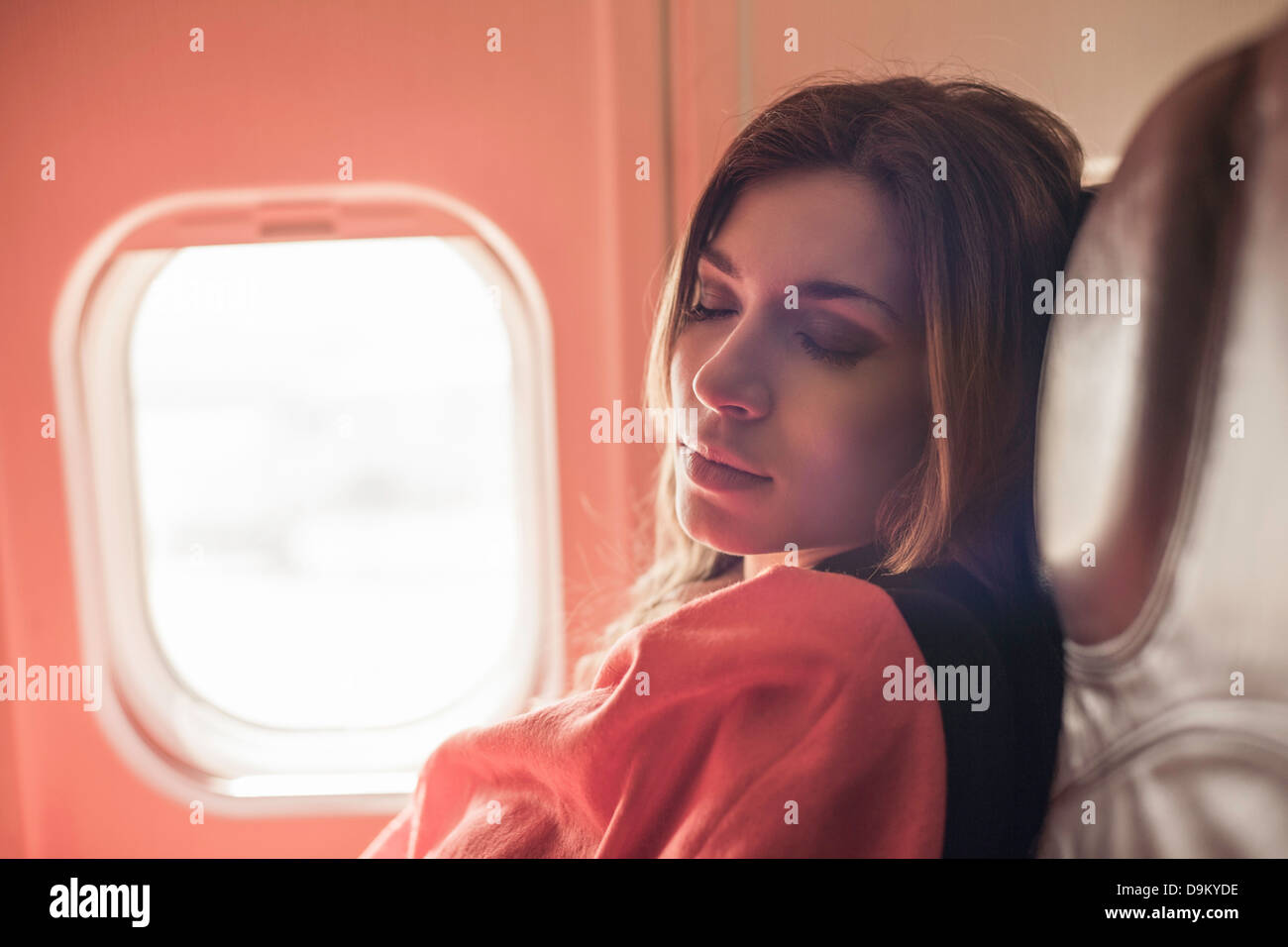 Female passenger asleep under blanket on aeroplane - Stock Image