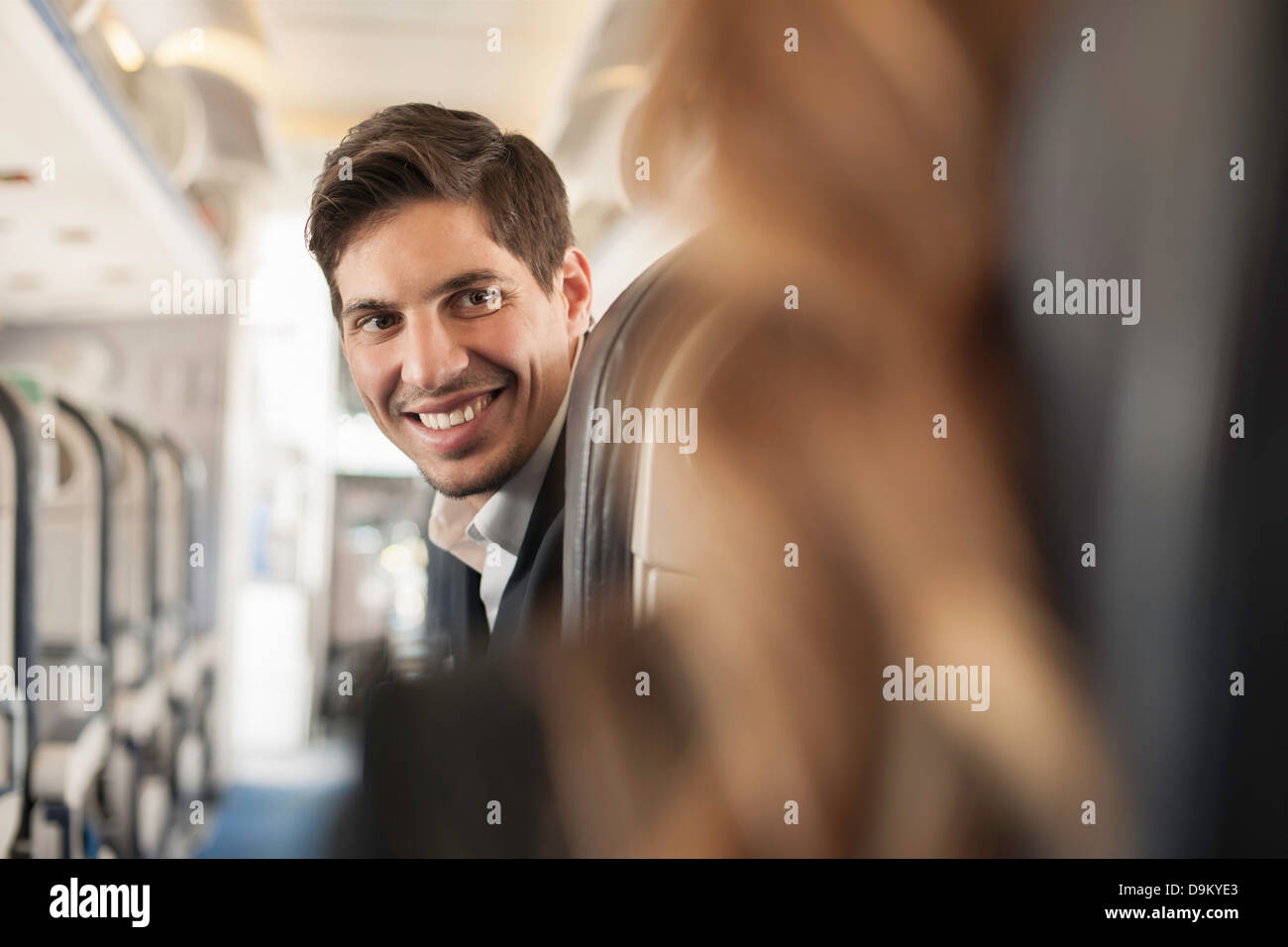 Male passenger turning around on aeroplane - Stock Image