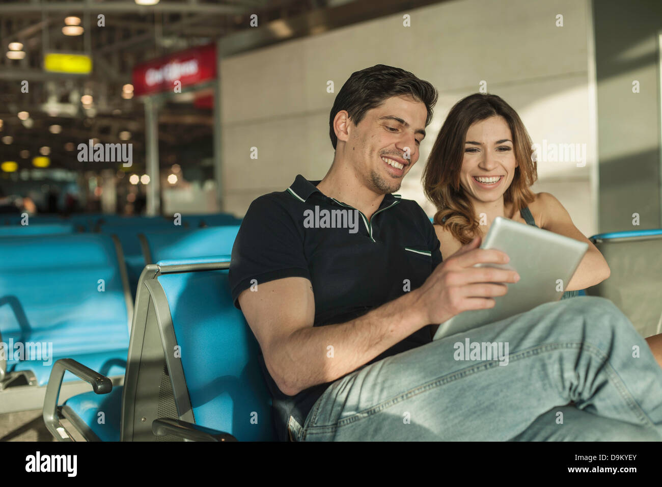 Young couple using digital tablet in airport departure lounge - Stock Image