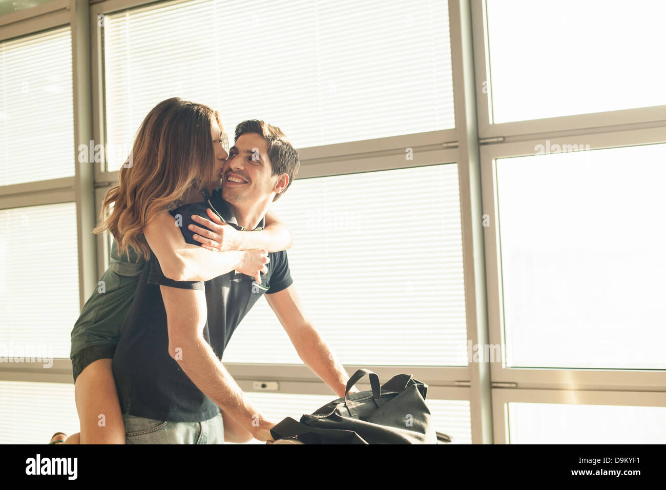 Young man giving woman piggy back in airport - Stock Image