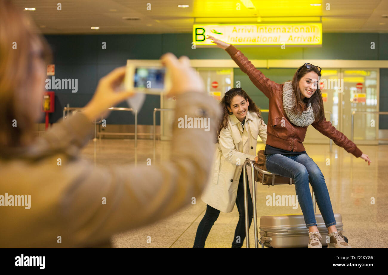 Woman photographing two teenage girls in airport - Stock Image