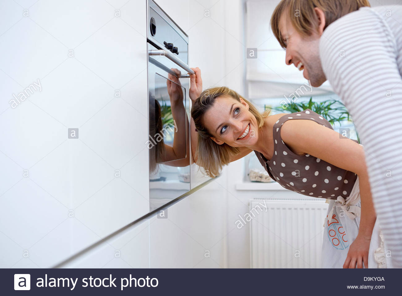Couple in kitchen, woman opening oven - Stock Image