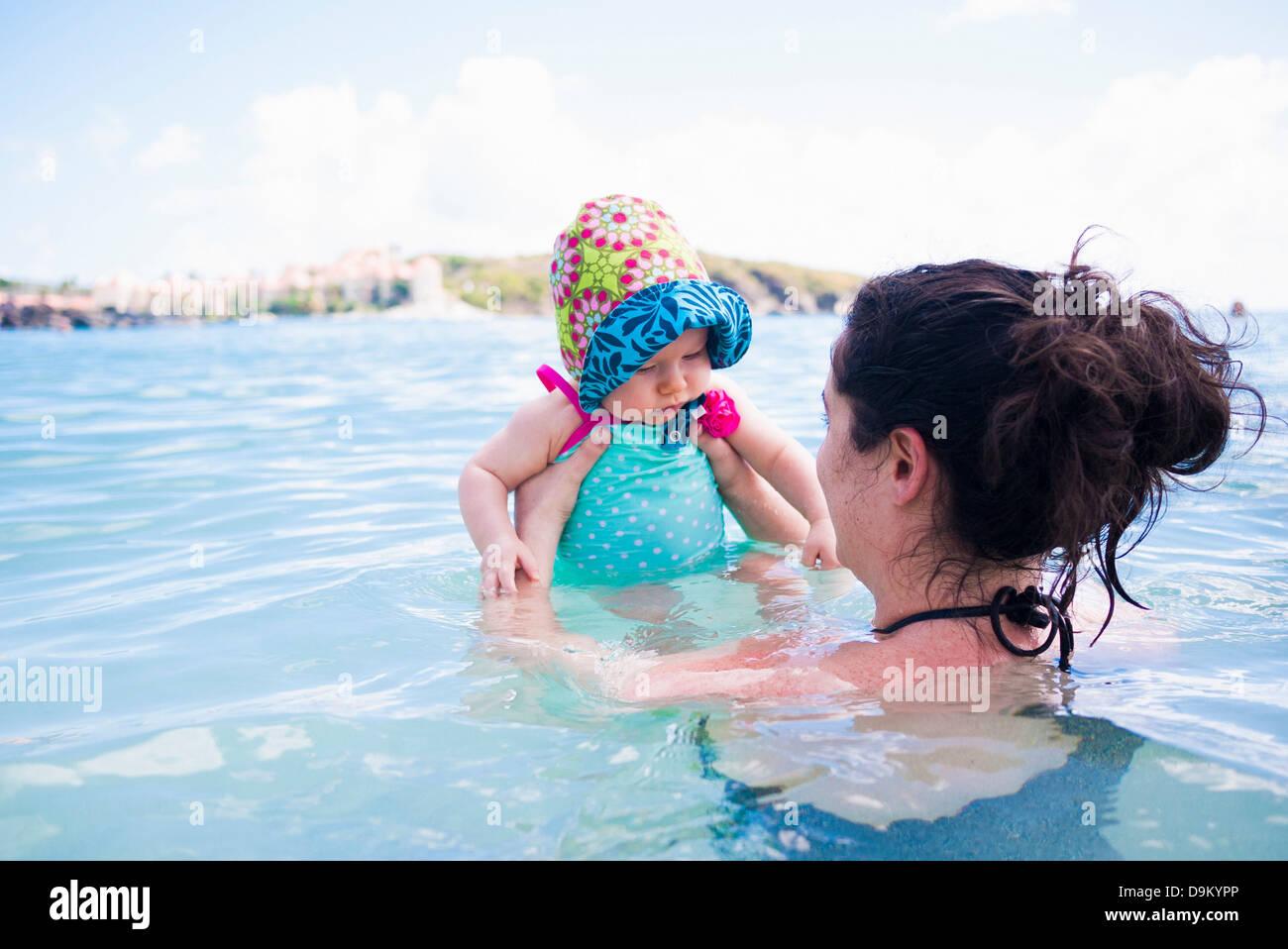 Mother holding baby daughter in sea, St Maarten, Netherlands - Stock Image