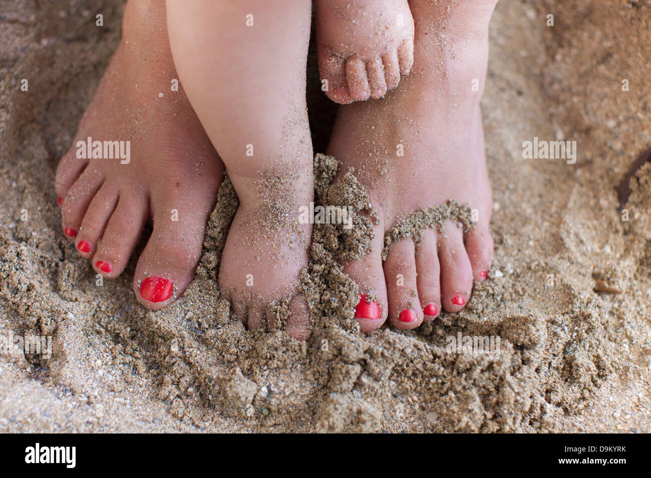 Mother with baby daughter's bare feet in sand - Stock Image