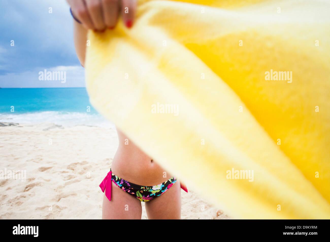 Woman holding yellow towel on beach, St Maarten, Netherlands - Stock Image