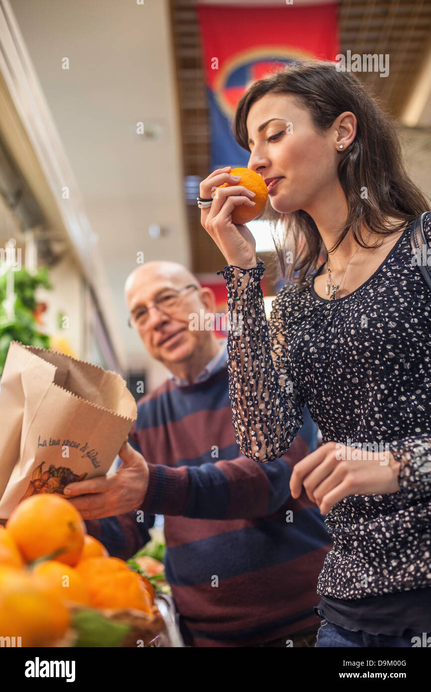 Woman smelling fresh oranges in market - Stock Image