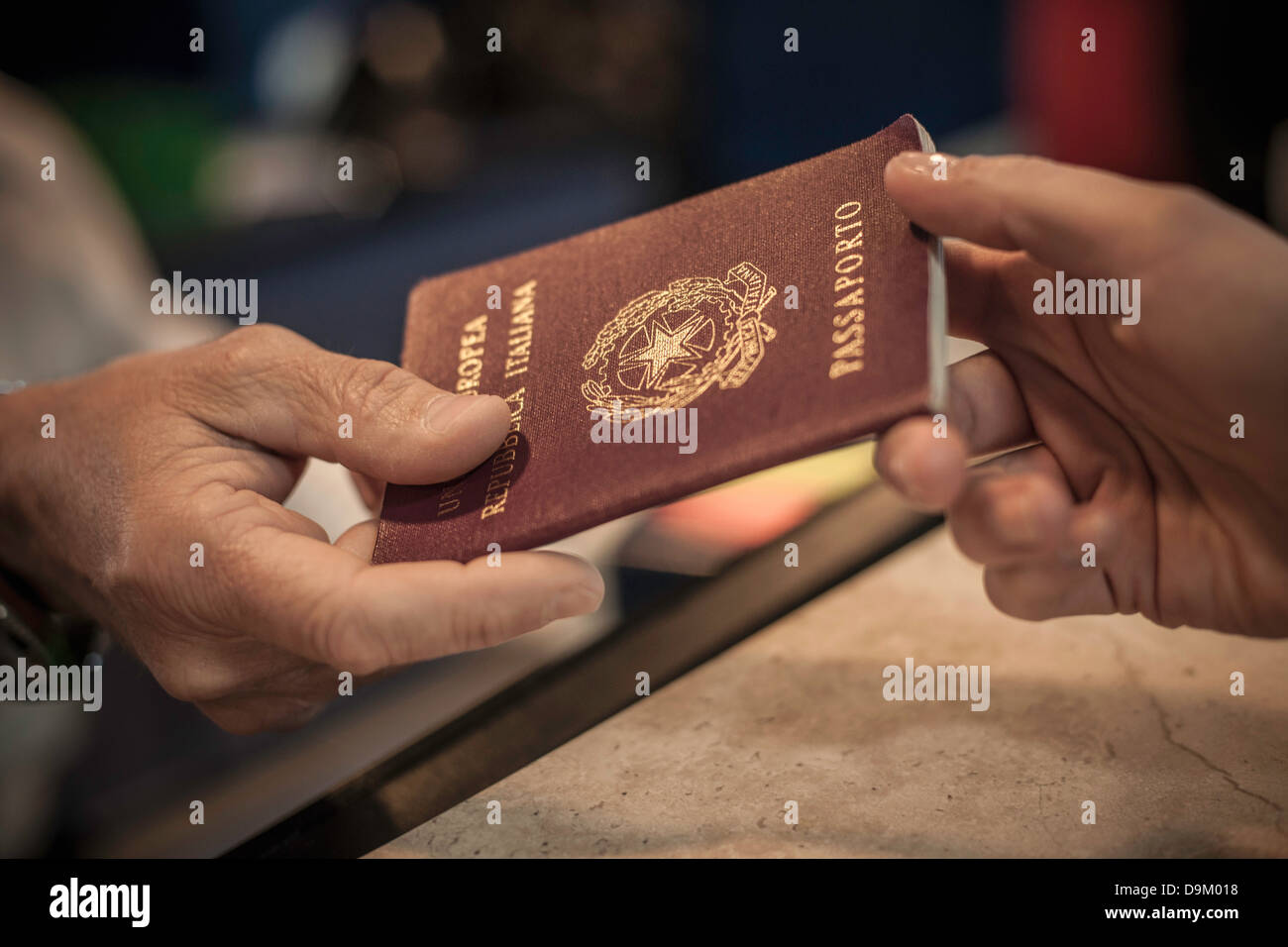 Person handing over passport, close up - Stock Image
