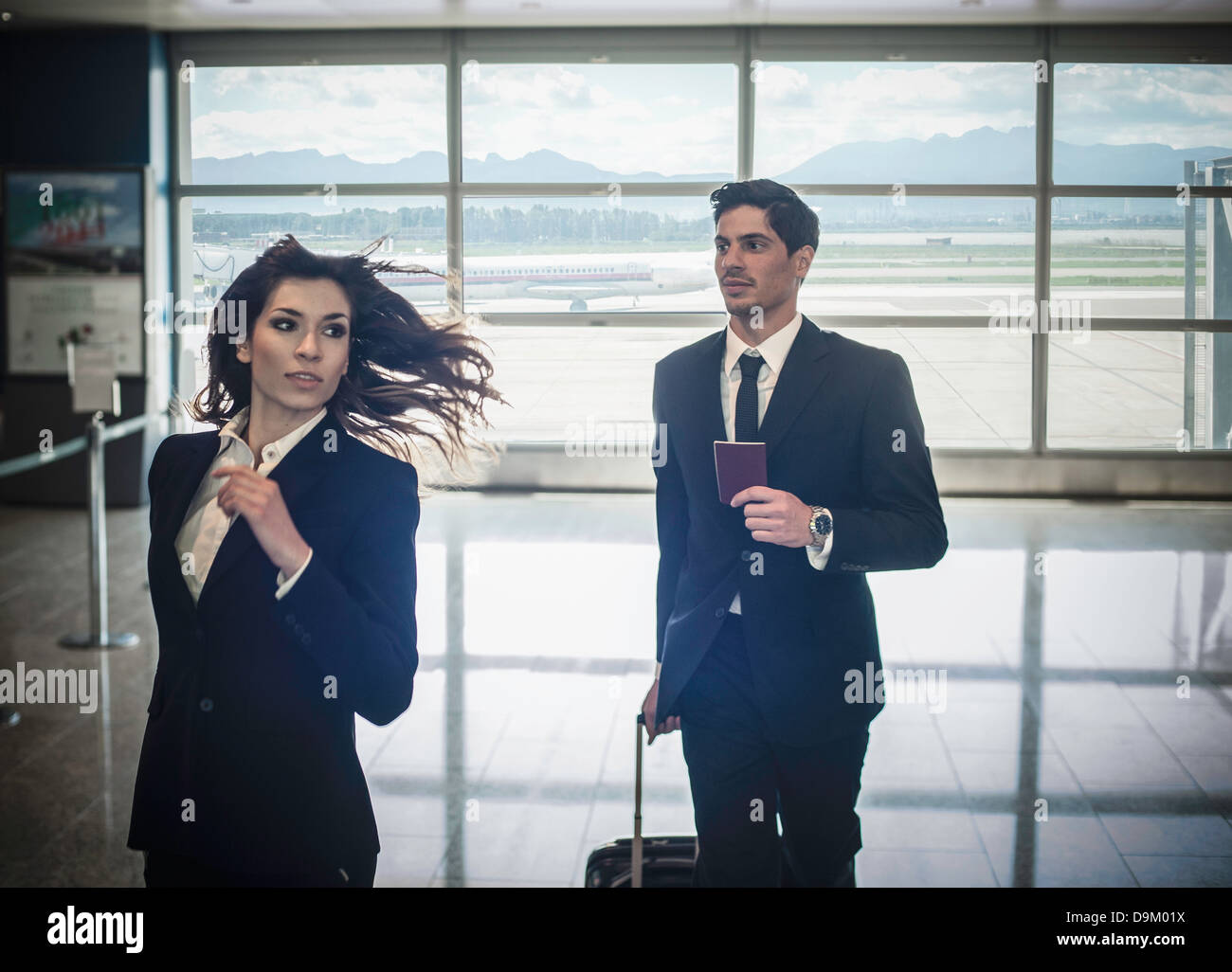 Businesspeople running in airport - Stock Image