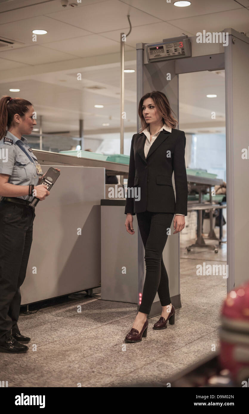 Security guard checking female passenger in airport security - Stock Image