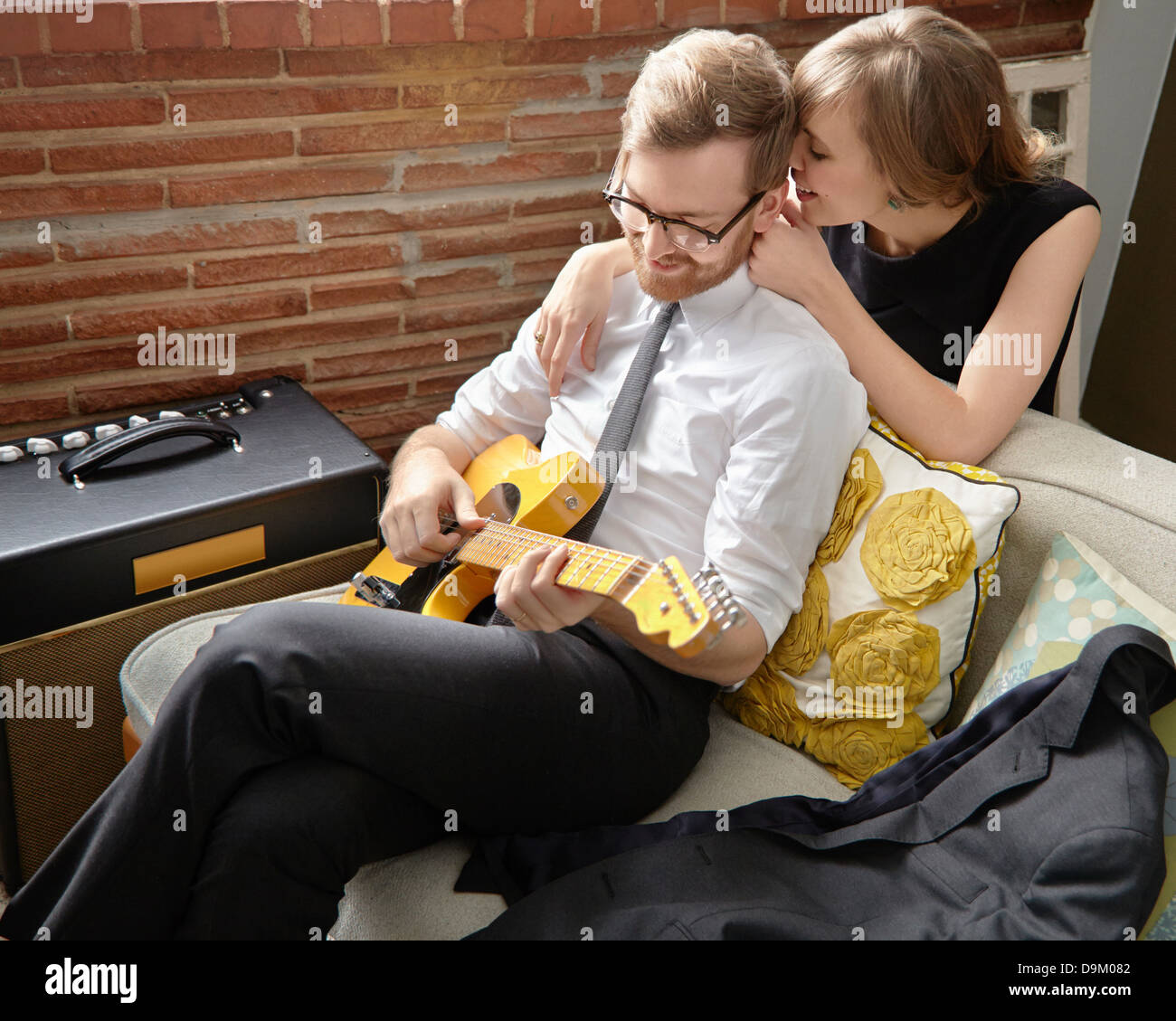 Young woman with partner practising on electric guitar - Stock Image