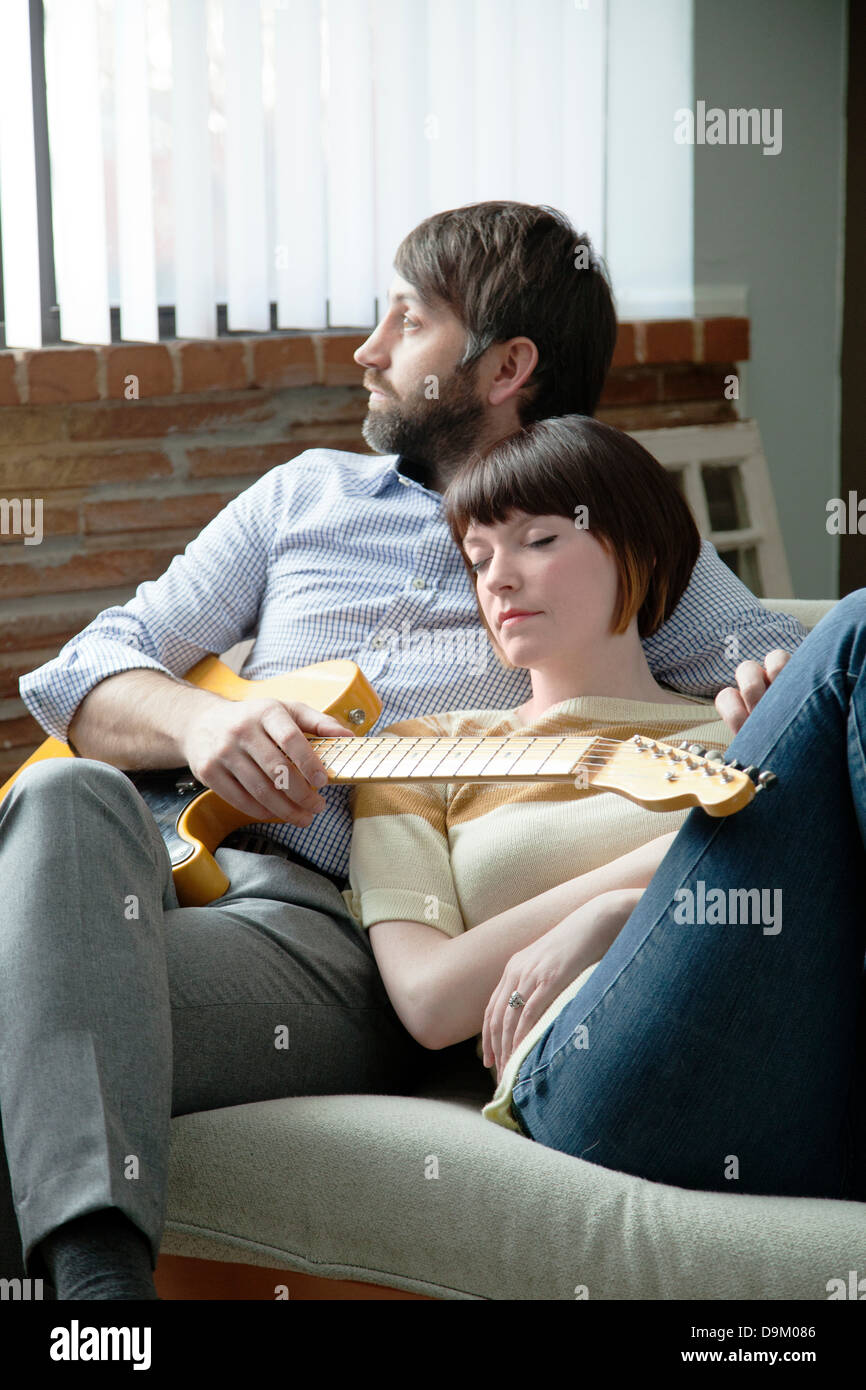 Young woman sleeping next to musician on sofa - Stock Image